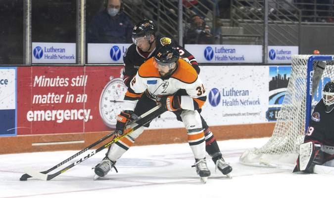 Michelle Davies | The Journal Gazette  The Komets' Morgan Adams-Moisan fights for control of the puck in the second period of Sunday's game at Memorial Coliseum.