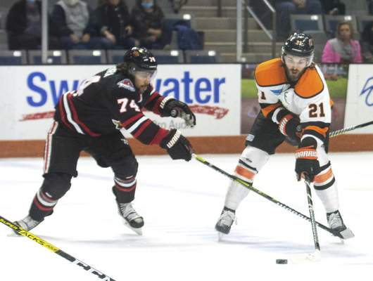 Michelle Davies | The Journal Gazette  The Komets' Maro-Olivier Roy keeps the puck away from Indy's Keoni Texeira in the first period of Sunday's game at Memorial Coliseum.