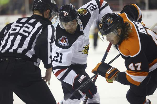Whiteshark Photography  Komets forward A.J. Jenks, right, battles for control of the puck with the Indy Fuel's Matt Marcinew during a faceoff Wednesday at Indianapolis.