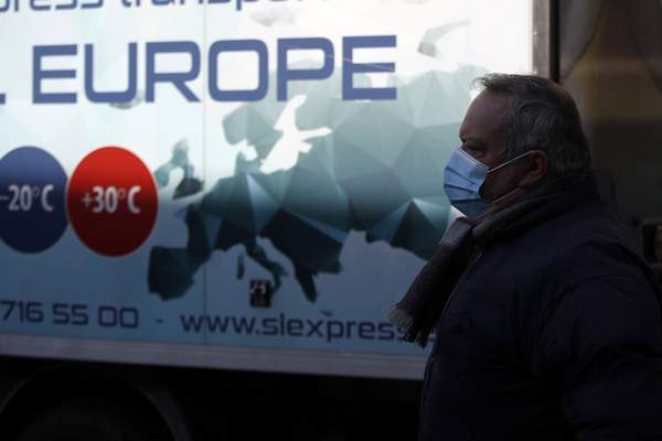 A man wearing a face mask to protect against the spread of the coronavirus, walks next to a truck in Athens, Wednesday, March 31, 2021. Despite five months of lockdown measures, COVID-19 infections on Tuesday hit a new record in Greece. (AP Photo/Thanassis Stavrakis)