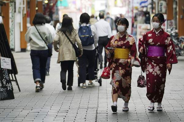 People wearing protective masks to help curb the spread of the coronavirus walk through a shopping arcade in the Asakusa district Wednesday, March 31, 2021, in Tokyo. The Japanese capital confirmed more than 410 new coronavirus cases on Wednesday. (AP Photo/Eugene Hoshiko)