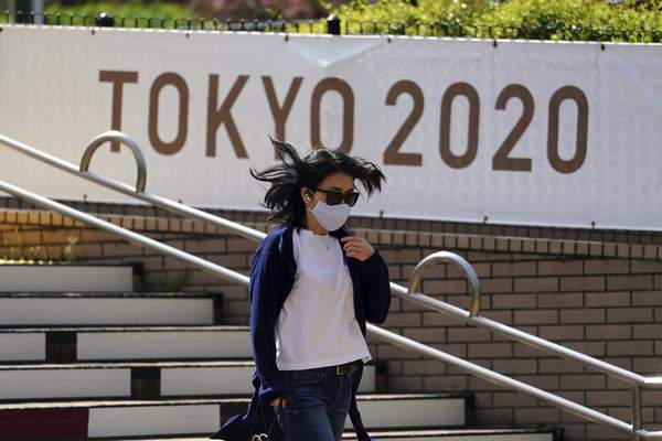 A woman wearing a protective mask to help curb the spread of the coronavirus walks near a banner for Tokyo 2020 Olympic and Paralympic Games Wednesday, March 31, 2021, in Tokyo. The Japanese capital confirmed more than 410 new coronavirus cases on Wednesday. (AP Photo/Eugene Hoshiko)