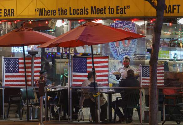 FILE - In this Nov. 24, 2020, file photo, patrons sit outdoors for dinner separated by plastic dividers with national flags at Mel's drive-in restaurant, in West Hollywood, Calif. Los Angeles County can reopen even more businesses while expanding how many people are allowed to dine indoors or catch a movie, California public health officials announced Tuesday, March 30, 2021. The county of 10 million people was one of several that moved into the state's orange tier, which is the second-least restrictive of California's four-tier system. (AP Photo/Damian Dovarganes, File)