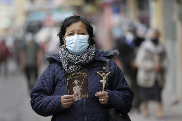Wearing masks to curb the spread of the new coronavirus, a parishioner walks behind as the statue of the Lord of Good Success during the Holy Week procession in Riobamba, Ecuador, Tuesday, March 30, 2021. Due to the COVID-19 pandemic, the sacred image did not have the crowds that usually accompany it in the procession. (AP Photo/Dolores Ochoa)