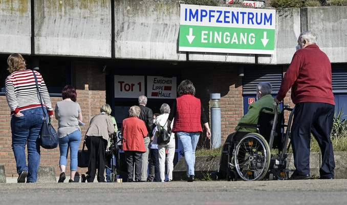 People wait in front of the vaccination center in Gelsenkirchen, Germany, Wednesday, March 31, 2021. German health officials have agreed to restrict the use of AstraZeneca's coronavirus vaccine in people under 60, amid fresh concern over unusual blood clots reported in a tiny number of those who received the shots. (AP Photo/Martin Meissner)
