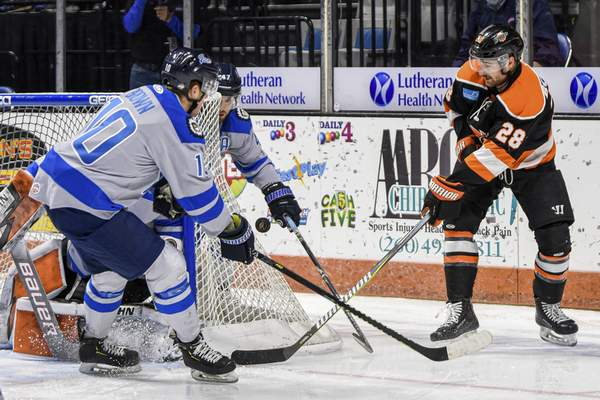 Mike Moore   The Journal Gazette Komets forward Matthew Boudens battles for the puck behind the Jacksonville goal Friday night.