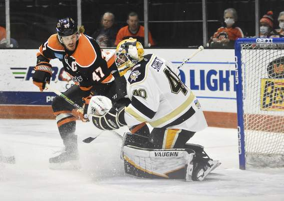 Katie Fyfe | The Journal Gazette  The Komets' A.J. Jenks hits the puck during the first period against Wheeling Nailers at Memorial Coliseum on Saturday.