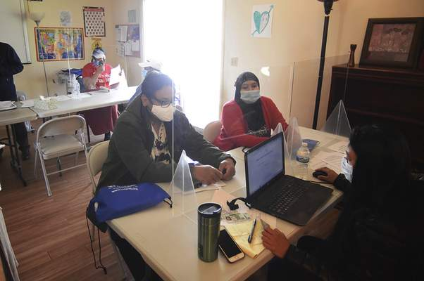 Spouses Da Zit Bai and Ra Si Da were among dozens who attended Wednesday's Catholic Charities-sponsored event to register former refugees for COVID-19 vaccinations.
