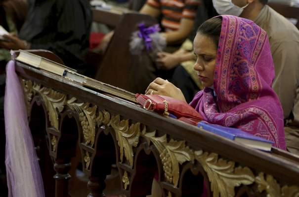 A Christian woman prays during an Easter mass at the St. John's Cathedral, in Peshawar, Pakistan, Sunday, April 4, 2021. (AP Photo/Muhammad Sajjad)