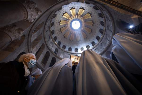 A woman wearing a face mask attends Easter Sunday mass led by Latin Patriarch of Jerusalem Pierbattista Pizzaballa at the Church of the Holy Sepulchre, where Jesus Christ is believed to be buried, in the Old City of Jerusalem, Sunday, April. 4, 2021. (AP Photo/Oded Balilty)