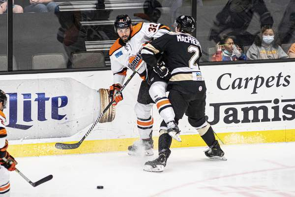 Zack Rawson | Special to The Journal Gazette Komets forward Morgan Adams-Moisan passes the puck as he's checked by the Wheeling Nailers' Dylan MacPherson on Wednesday in Wheeling, West Virginia.