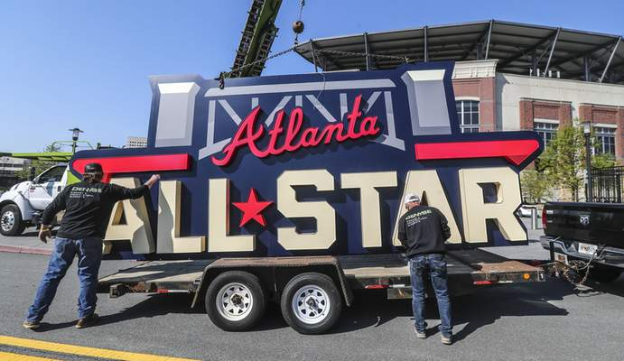 Workers load an All-Star sign onto a trailer after it was removed from Truist Park in Atlanta, Tuesday, April 6, 2021. Major League Baseball plans to relocate the All-Star Game to Coors Field in Denver after pulling this year's Midsummer Classic from Atlanta over objections to sweeping changes to Georgia's voting laws, according to a person familiar with the decision. The person spoke to The Associated Press on condition of anonymity Monday night, April 5, 2021, because MLB hadn't announced the move yet. (John Spink/Atlanta Journal-Constitution via AP)