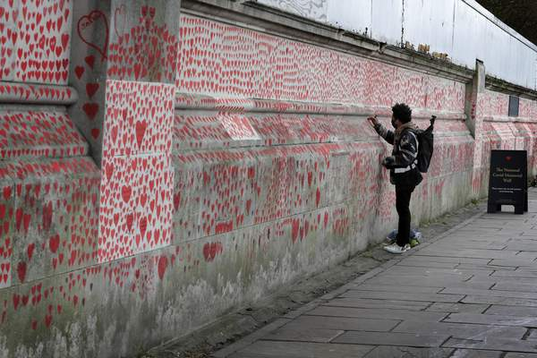 A man paints red hearts onto the COVID-19 Memorial Wall mourning those who have died, opposite the Houses of Parliament on the Embankment in London, Wednesday, April 7, 2021. Hearts are being painted onto the wall in memory of the many thousands of people who have died in the UK from coronavirus. (AP Photo/Kirsty Wigglesworth)