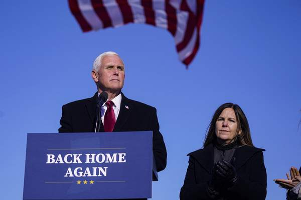 FILE - In this Jan. 20, 2021, file phot, former Vice President Mike Pence speaks after arriving back in his hometown of Columbus, Ind., as his wife Karen watches. Pence is steadily re-entering public life as he eyes a potential run for the White House in 2024. (AP Photo/Michael Conroy, File)