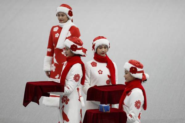 Chinese attendants dressed in winter costumes rehearse the award ceremony of the men's 500-meters race during a test event for the 2022 Beijing Winter Olympics at the National Speed Skating Oval in Beijing, Wednesday, April 7, 2021. (AP Photo/Andy Wong)