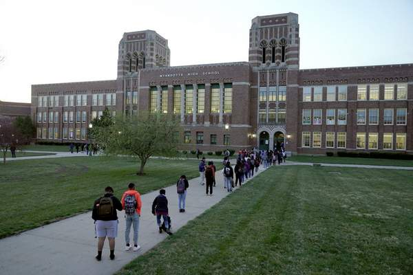 FILE - In this Wednesday, March 31, 2021, file photo, students wait to enter Wyandotte County High School in Kansas City, Kan., on the first day of in-person learning. (AP Photo/Charlie Riedel, File)