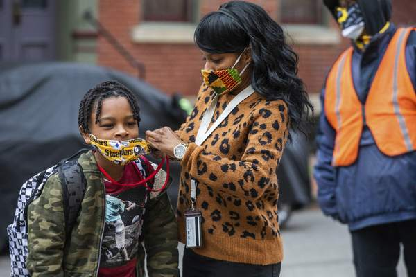 FILE - In this Monday, March 29, 2021, file photo, Jenea Edwards, of the North Side, helps her son Elijah, 9, in the third grade, with his mask before heading into Manchester Academic Charter School on the first day of in-person learning via a hybrid schedule, in Pittsburgh. (Andrew Rush/Pittsburgh Post-Gazette via AP, File)