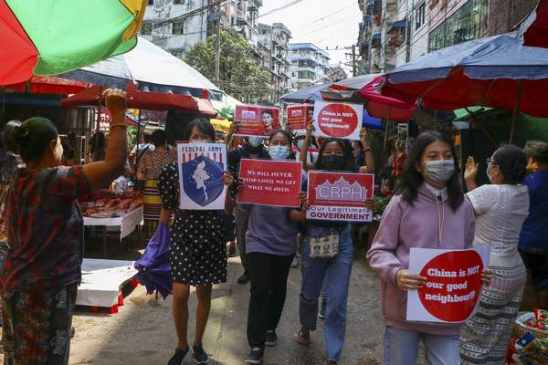 Anti-coup protesters hold slogans as they are greeted while marching along a market street in Yangon, Myanmar, Wednesday April 7, 2021. (AP Photo)