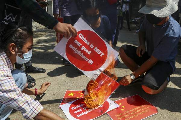 Anti-coup protesters burn a representation of the Chinese national flag during a demonstration in Yangon, Myanmar on Wednesday, April 7, 2021. (AP Photo)