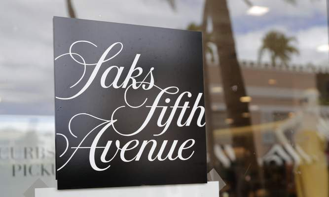 FILE - In this May 11, 2020 file photo, a Saks Fifth Avenue store remains closed on Worth Ave. during the new coronavirus pandemic in Palm Beach, Fla. (AP Photo/Lynne Sladky, File)