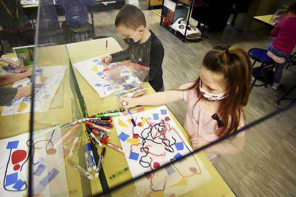 Katie Fyfe | The Journal Gazette Masked kindergartners Ferris Henriksen and Grace Crupe – separated by Plexiglas – get creative at Perry Hill Elementary School in January.
