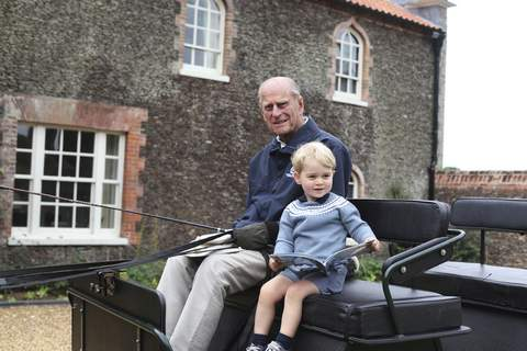 Britain Prince Philip In this undated handout photo provided by the Duke and Duchess of Cambridge, Britain's Prince Philip sits with his great-grandson Prince George in England. Prince Philip, the irascible and tough-minded husband of Queen Elizabeth II who spent more than seven decades supporting his wife in a role that mostly defined his life, died on Friday, April 9, 2021. (Duke and Duchess of Cambridge via AP) (HONS)