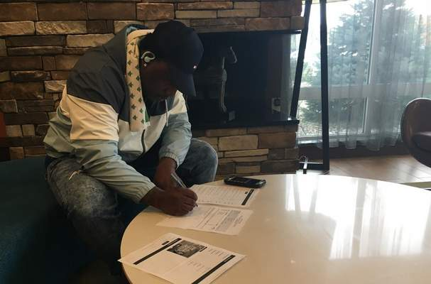 Dylan Sinn | The Journal Gazette  National Gridiron League player Atavius Matthews looks at his hotel invoices for the weekend as he tries to determine how much the NGL should reimburse him. He told the Journal Gazette he spent $910 in hotel and travel costs to get to Fort Wayne to play in the league.