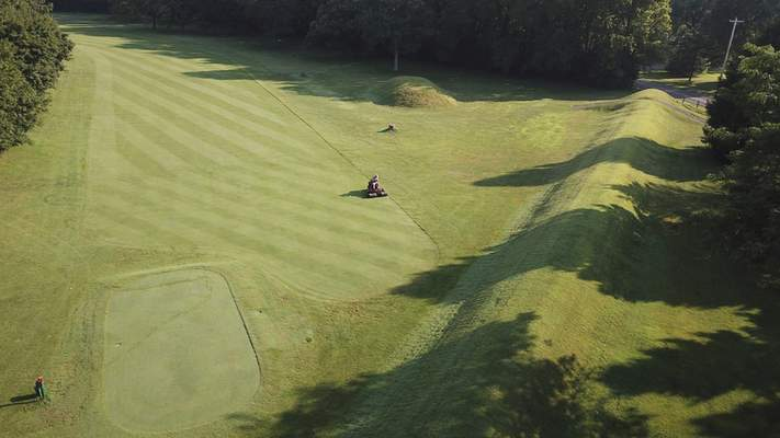 This photo made on July 30, 2019 shows a groundskeeper as he mows near the flat-topped mound that is part of the 50-acre octagon at Moundbuilders Country Club at the Octagon Earthworks in Newark, Ohio. (Doral Chenoweth III/The Columbus Dispatch via AP,)