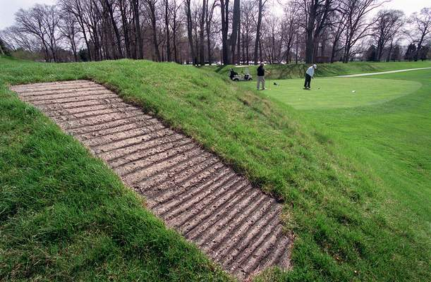 FILE - This April 6, 2000 file photo shows a concrete walkway, foreground, that allows golfers access to the top of an ancient American Indian mound at Moundbuilders Country Club in Newark, Ohio. (Jeff Adkins/The Columbus Dispatch via AP, File)