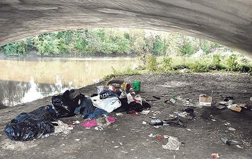 File Evidence of a homeless encampment is visible under a Main Street bridge in 2018.
