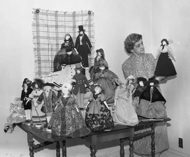 Mrs. J.A. Stover stands with most of her collection of 20 dolls dressed in authentic 18th and 19th century costumes. The pair with white wigs in the center front are wearing costumes of 1775 and on the left are a man and woman of the Empire period around 1800. In the second row from the bottom, the man and woman have 1830 costumes on. The third row shows two dolls wearing the Princess styles of 1867 and the two dolls at the top are modeling the fashions of 1860. (Journal Gazette file photo)