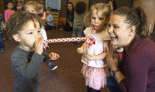 Michelle Davies | The Journal Gazette Jordan Knight, 2, blows a noisemaker Monday morning at The Learning Community's Music Monday to celebrate Week of the Young Child. Right is Amanda Housholder, lead teacher, and Chole Hale, 2.