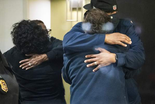 People hug Friday after learning their loved one is safe after the shooting, which left eight people dead.