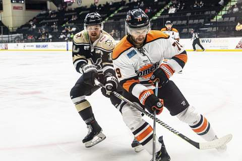 Zack Rawson | Special to The Journal Gazette Komets defenseman Marcus McIvor, front, chases the puck in the corner as he's followed by the Wheeling Nailers' Austin Fyten on Sunday in Wheeling, West Virginia.