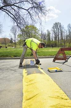 Katie Fyfe   The Journal Gazette Greg Reith of the Fort Wayne Parks and Recreation Department paints over the speed bumps at Franke Park on Monday afternoon.