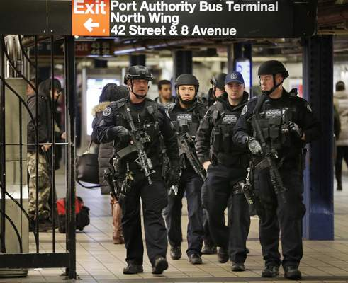 FILE †In this Dec. 12, 2017 file photo, police officers patrol in the passageway connecting New York City's Port Authority bus terminal and the Times Square subway station, near the site of an explosion the previous day. (AP Photo/Seth Wenig, File)