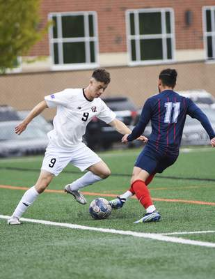 Katie Fyfe | The Journal Gazette  Indiana Tech sophomore Luke Jones advances the ball while Cumberlands junior Alejandro Gonzalez defends during the first half at Indiana Tech on Saturday.
