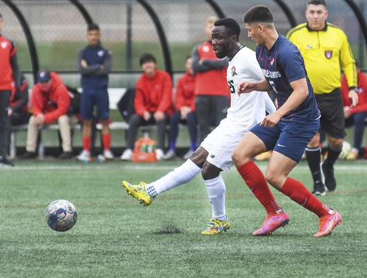 Katie Fyfe | The Journal Gazette  Indiana Tech senior Maxwell Amoako and Cumberlands freshman Gabriel Figurski chase the ball during the first half at Indiana Tech on Saturday.