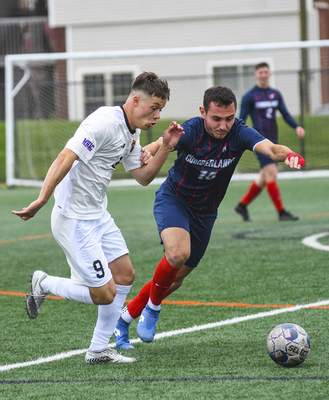 Katie Fyfe | The Journal Gazette  Indiana Tech sophomore Luke Jones and Cumberlands senior Sergio Infantes Castell chase the ball during the first half at Indiana Tech on Saturday.
