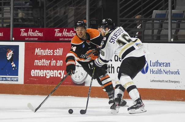 Katie Fyfe | The Journal Gazette  Komets forward Stephen Harper and the Wheeling Nailers' Cody Sylvester chase the puck during the first period at Memorial Coliseum on Saturday.