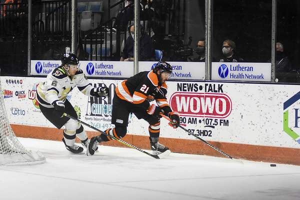 Katie Fyfe | The Journal Gazette Komets forward Marc-Olivier Roy carries the puck with the Nailers defenseman Adam Smith in pursuit Saturday night at the Coliseum.