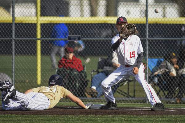 Mike Moore | The Journal Gazette Bishop Dwenger's Brayton Thomas dives into first base as North Side first baseman Christian Cox readies the catch in the third inning at the World Baseball Academy on Thursday.