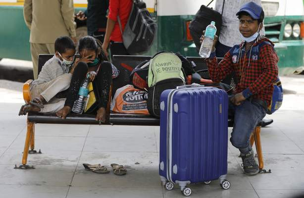 Children of migrant workers wait for transportation at a bus station during a lockdown in New Delhi, India, Friday, April 30, 2021. Indian scientists appealed to Prime Minister Narendra Modi to publicly release virus data that would allow them to save lives as coronavirus cases climbed again Friday, prompting the army to open its hospitals in a desperate bid to control a massive humanitarian crisis. (AP Photo)