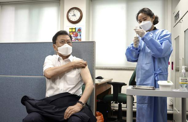 South Korean President Moon Jae-in, left, sits in a chair to receive his second dose of the AstraZeneca COVID-19 vaccine at a health care center in Seoul, South Korea, Friday, April 30, 2021. (Lee Jin-wook/Yonhap via AP)
