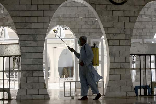 A worker disinfects a mosque ahead of Friday prayer in an effort to contain the outbreak of the coronavirus during the Muslim fasting month of Ramadan, in Karachi, Pakistan, Friday, April 30, 2021. (AP Photo/Fareed Khan)