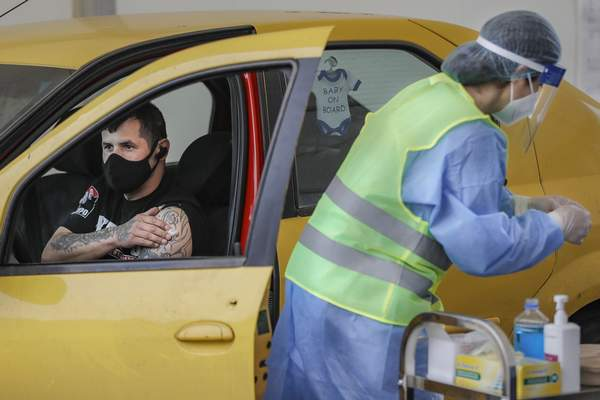 A man waits in his car after receiving a Pfizer COVID-19 vaccine at the first drive-through vaccination center in Bucharest, Romania, Thursday, April 29, 2021. (AP Photo/Vadim Ghirda)