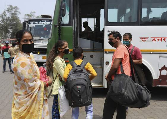 Migrant workers and their children wait for transportation at a bus station during the lockdown in New Delhi, India, Friday, April 30, 2021. Indian scientists appealed to Prime Minister Narendra Modi to publicly release virus data that would allow them to save lives as coronavirus cases climbed again Friday, prompting the army to open its hospitals in a desperate bid to control a massive humanitarian crisis. (AP Photo)