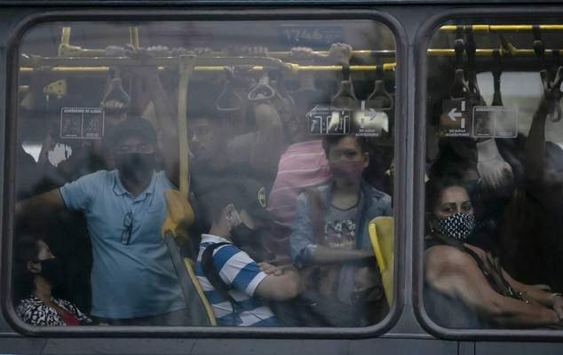 FILE - In this March 30, 2021 file photo, commuters wearing protective face masks amid the COVID-19 pandemic, ride in a crowded public bus, in Rio de Janeiro, Brazil. Public health experts say that restrictions on activity and social distancing can help ease pressure on hospitals' overloaded intensive care units, but that the only long-term solution is mass vaccination in a country of 210 million people that is bigger than the contiguous U.S. (AP Photo/Bruna Prado, File)