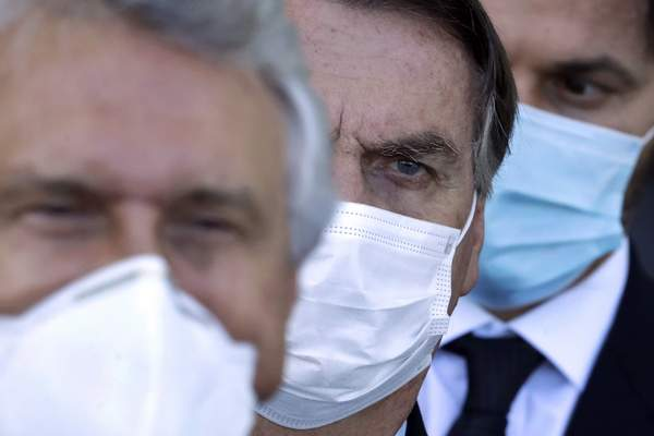 FILE - In this March 24, 2021 file photo, Brazilian President Jair Bolsonaro, center, arrives for a press conference following a meeting about the federal government's response to the COVID-19 pandemic at the presidential residence Alvorada Palace in Brasilia, Brazil. Tightened public health measures remain anathema to Bolsonaro; he has called lockdown measures absurd. (AP Photo/Eraldo Peres, File)