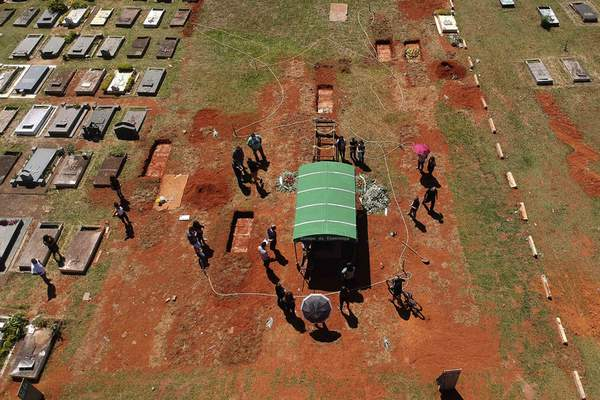 A family attends the burial service for David Ferreira Gomes, who died from complications related to COVID-19, at the Campo da Esperanca cemetery in Brasilia, Brazil, Friday, April 16, 2021. Brazil marked a milestone of 400,000 COVID-19 deaths Thursday, April 29, 2021, the world's second-highest tally, with the majority recorded in just the last four months. (AP Photo/Eraldo Peres)